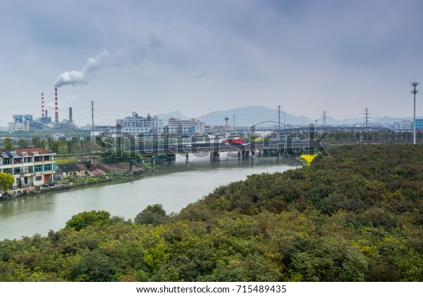 Modern factory area with background of smoke pollution and river  in Ningbo City, Zhejiang, China