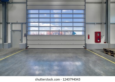 A modern factory. Large entrance gates with transparent glass windows.