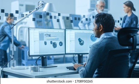 Modern Factory Office: Automotive Engineer Working on PC with Screen Showing 3D Car Concept Made in CAD. Workshop: Workers Use High-Tech Industrial CNC Machinery, Program Robot Arm, Have Meeting
