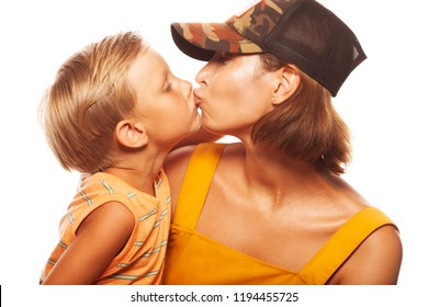 Modern family concept. Portrait of fashionable mother kissing her gorgeous baby boy in trendy gimme cap, isolated on white background. Stylish casual clothes. Studio shot