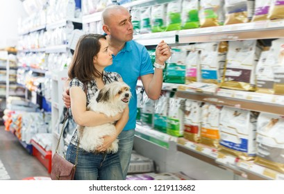 Modern family couple with dog  buying dry food for dogs in pet shop