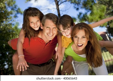 A modern family of father, mother, daughter and son playing together and having fun doing piggy back in a park