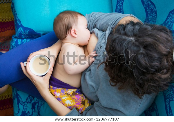 Modern family lifestyle. Aerial view of a woman giving baby breastfeeding having a coffee