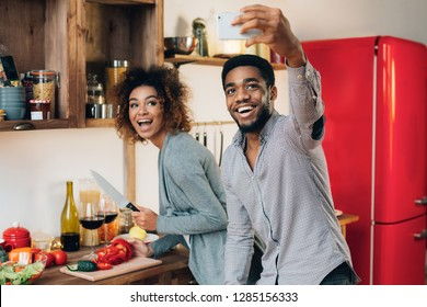 Modern family lifestyle. Happy young african-american couple in kitchen taking selfie on smarphone, preparing healthy food.