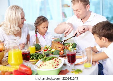 Modern family sitting at festive table and going to eat roasted turkey, young man cutting it