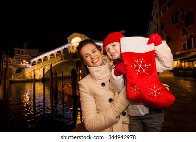 Modern family take the best of Christmas season by having a fascinating trip to Venice, Italy. Happy mother and daughter showing Christmas sock in the front of Rialto Bridge