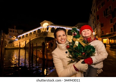 Modern family take the best of Christmas season by having a fascinating trip to Venice, Italy. Portrait of happy mother and daughter with Christmas tree in the front of Rialto Bridge