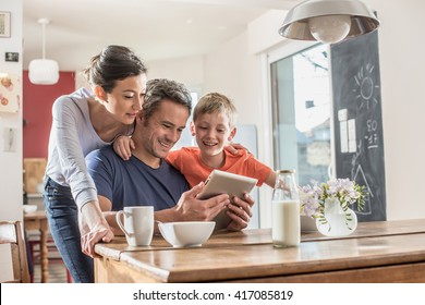 A modern family using a digital tablet while having breakfast in the kitchen, mom,  dad and their eight year old son