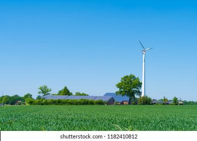 modern farmhouse with solar panels and a wind turbine