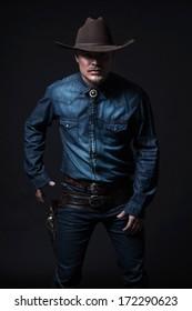 Modern fashion cowboy. Wearing brown hat and blue jeans shirt. Pulling his gun. Blonde hair and beard. Studio shot against black.