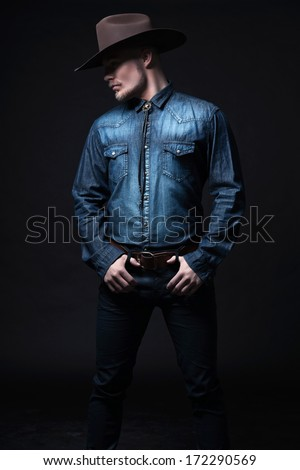 0af0c4c6fe706 Modern fashion cowboy. Wearing brown hat and blue jeans shirt. Blonde hair  and beard