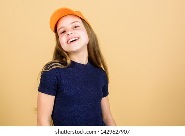 Modern fashion. Hat or cap. Stylish accessory. Kids fashion. Feeling confident with this cap. Girl cute child wear cap or snapback hat beige background. Little girl wearing bright baseball cap.