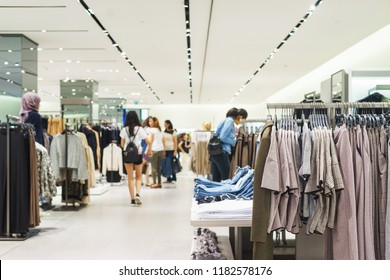 Modern fashion store. Buyers choose the right clothes. Fashionable men's and women's clothes on hangers in a clothing store. Sale and shopping in stores. Soft focus.