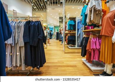 Modernes Modegeschäft. Käufer wählen Kleidung aus. Shirts, Hoodies, Blusen und Halbpullover, ein Pullover auf einem Hänger in einem Kleiderladen, Nahaufnahme. Verkauf und Einkauf in Geschäften. Weicher Fokus.
