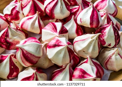 Modern fashion trend : fruit meringues. Colorful, striped  meringue kisses flavored with seedless raspberry jam.