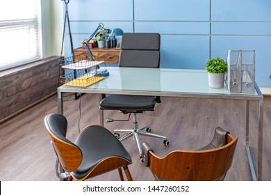 Modern fashionable design of a personal office of the studio is decorated with a blue wall with a seating area