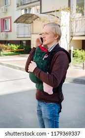 Modern father carrying baby in sling or ergo backpack, using mobile phone near the house
