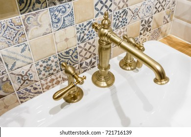 Modern faucet of brass color and sink in bathroom interior