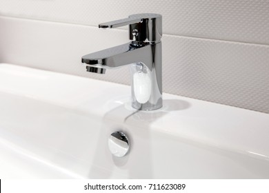 Modern faucet of chrome color in bathroom interior