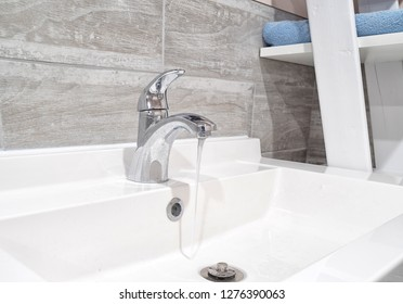 Modern faucet with running water in a bathroom