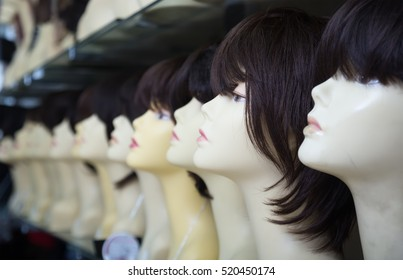 modern female mannequins with wigs on shelves of hair salon