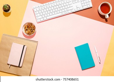 Modern feminine home workspace. Flat lay composition of keyboard, cactus, diaries with pen, nuts, and cup of tea on colorful desk. Pink, yellow, aquamarine and and brown colours. Blogger's home office