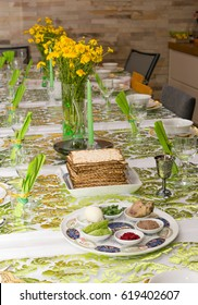 Modern festive Passover Seder table with green  and gold decorations in Tel Aviv, Israel, complete with Matzos and a traditional Seder Plate.