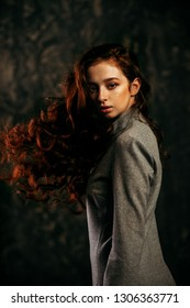 Modern  fifteen-year-old girl with long curly red hair posing over grunge background. Beauty, fashion.