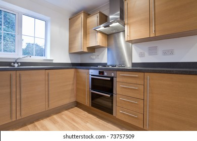 Modern fitted kitchen units within new home including built-in appliances