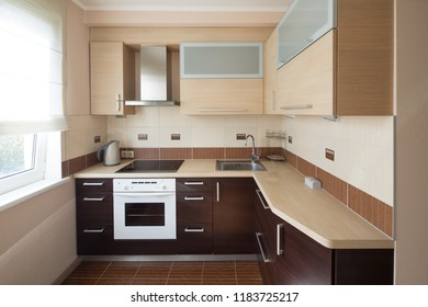Modern flat interior with laminate and warm tones. Kitchen
