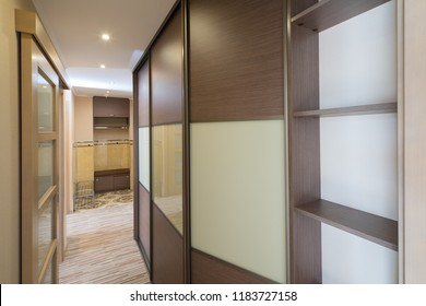 Modern flat interior with laminate and warm tones. Built-in wardrobe