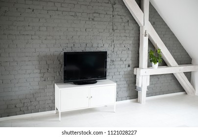 Modern flat lcd television set on white cabinet. Grey brick wall and wooden ceiling beams. Modern, bright attic apartment.