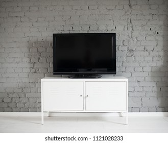 Modern flat lcd television set on white cabinet. Grey brick wall. Modern, bright attic apartment.