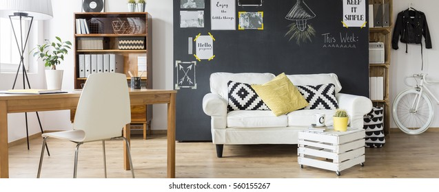 Modern flat with wooden desk, chair, DIY small table, sofa and blackboard, panorama