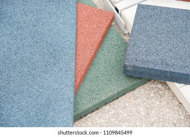 Modern floor covering in the form of rubber tiles and details of red, green and blue