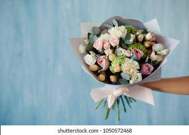 Modern flower arrangement bouquet of roses in kraft paper is holding girl against blue wall background.