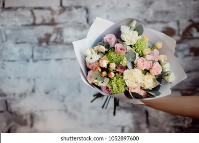 Modern flower arrangement bouquet of roses in kraft paper is holding girl against brick wall background.