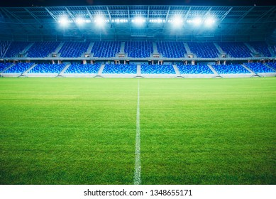 Modern Football Stadium in the evening. Soccer arena, background. Green grass, blue seats