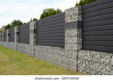 A modern form of house fencing. Gabions, steel galvanized nets filled with split stone