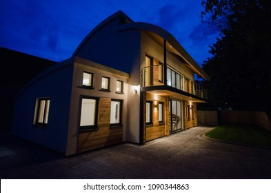 Modern four bedroom detached family home at night with the lights on.