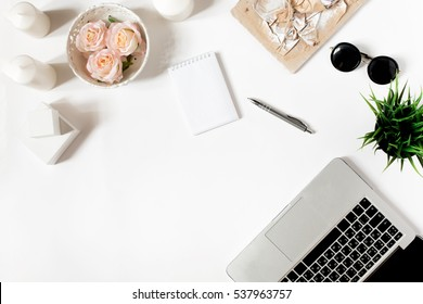 Modern frame with laptop keyboard, vintage tray with roses, office plant, notebook, sunglasses in flat lay style. White background. Top view.
