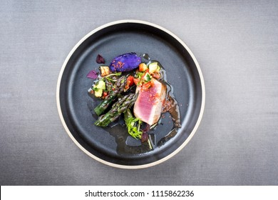 Modern fried tuna fish filet with green asparagus blue potatoes und vegetable chili relish as top view on a plate with copy space