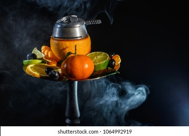 Modern fruit Hookah bowl with orange and a lot of fresh fruits with kaloud with red hot coconut coals charcoal with a lot of smoke at black background isolated. Smoking at dark shisha lounge