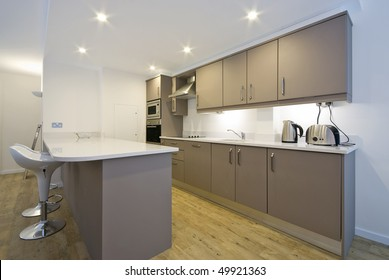 Modern fully fitted kitchen with appliances and bar seating in white