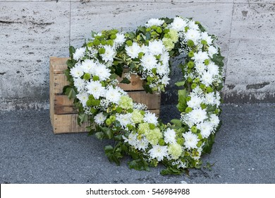 Modern funeral wreath made of white chrysanthemums in flower market Heart shaped funeral wreath in white and green color