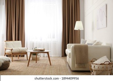 Modern furniture and window with curtains in stylish room interior