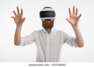 Modern futuristic technology and lifestyle concept. Studio portrait of unrecognizable young businessman with thick ginger beard using 3d goggles, experiencing visual reality, gesturing emotionally