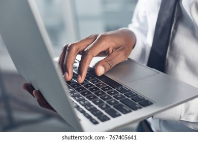 Modern gadget. Close-up of hand of young african businessman is holding laptop and typing on keyboard while standing in his office