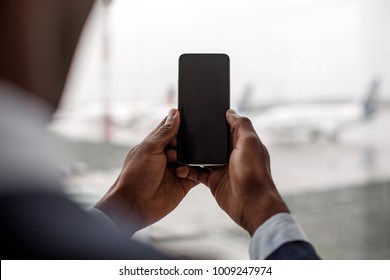 Modern gadget. Close-up of screen of smartphone in hands of african businessman. He is keeping device against window