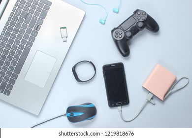 Modern gadgets and devices on a gray background. Laptop,power bank, earphones, smart bracelet, gamepad, headphones, USB flash drive, PC mouse. Flat lay